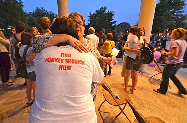 friends of mickey shunick console each other during candlelight vigil