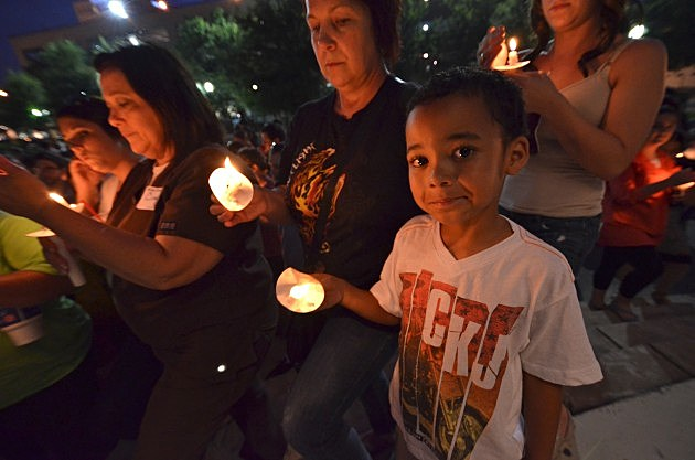 young boy holds candle at candlelight vigil for mickey shunick