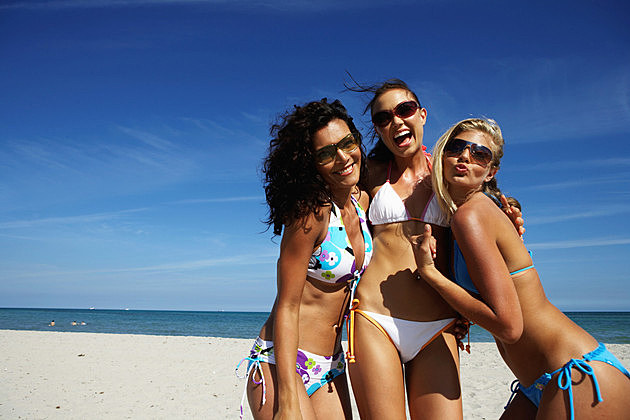 Three young women smiling on beach, portrait, close-up